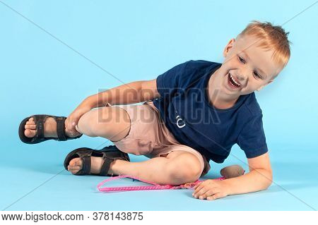 Pretty Little Caucasian Boy Falling Down On Blue Background, Cheerfully Laughing. Blond Hair, Casual