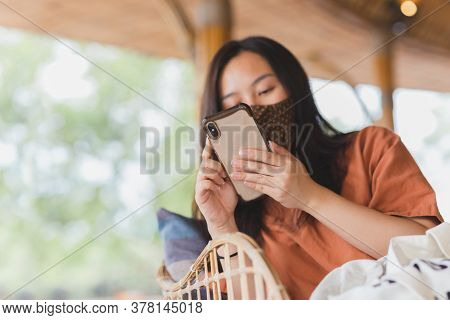 Woman In Face Mask Using Her Mobile Phone While Sitting In A Chair.