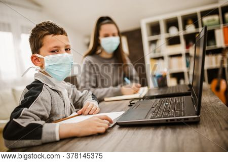 Boy And Girl Studies At Home, Wear Protective Masks, And Doing School Homework. Distance Learning On