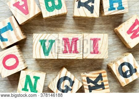 Alphabet Letter Block In Word Vmi (abbreviation Of Vendor Managed Inventory) With Another On Wood Ba