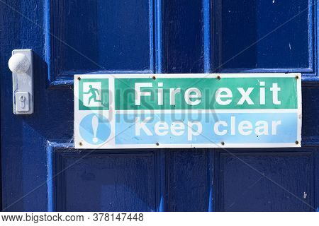 Fire Exit Keep Clear Sign On Building Blue Exit Door