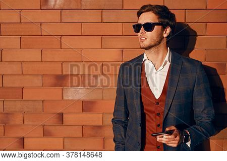 Trendy Smart Guy In Sunglasses And Suit Browsing Smartphone And Looking Away While Standing Near Bri