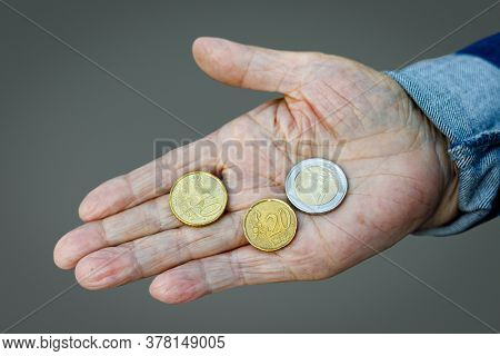 Coins In The Hand Of The Old Lady. An Elderly Woman With Money In Her Hands. Poverty Alms.