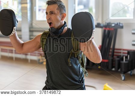Motivated Boot Camp Instructor Stands With Punch Mitts In Gym Hall. Training With Extended Arm On Wo