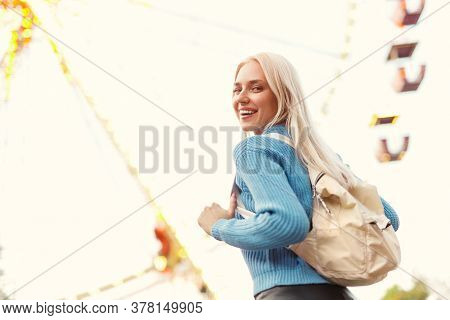From Below Excited Blond Woman With Backpack Smiling And Looking At Camera Over Shoulder While Havin