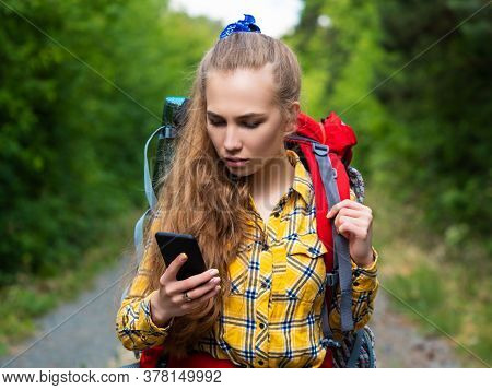 Closse-up Portrait Of A Woman, Who Lost In Forest. Lost In Forest And Using Gps App In Mobile Phone.