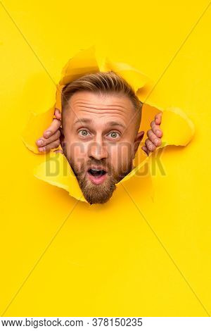Amazed Bearded Guy Looking At Camera In Astonishment While Ripping Hole In Vivid Yellow Paper