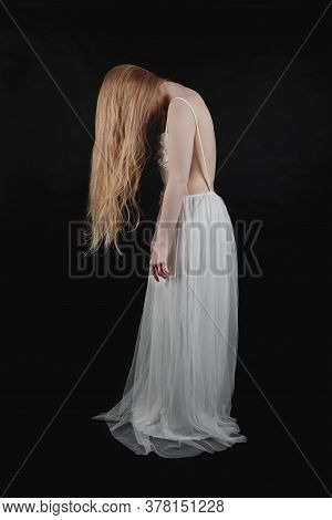 Young Blonde Girl Tilted Her Head Her Hair Hanging Over The Black Background
