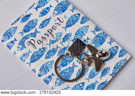 Close Up Passoprt Cover With Fishes Image And Metal Trinket In A Shape Of A Plane. Isolated On White
