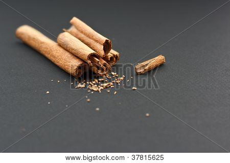 Cinnamon Sticks And Ground Flakes On Grey Background