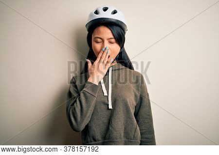 Young beautiful chinese woman wearing bike helmet over isolated white background bored yawning tired covering mouth with hand. Restless and sleepiness.