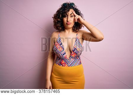 Young beautiful arab woman on vacation wearing swimsuit and sunglasses over pink background worried and stressed about a problem with hand on forehead, nervous and anxious for crisis