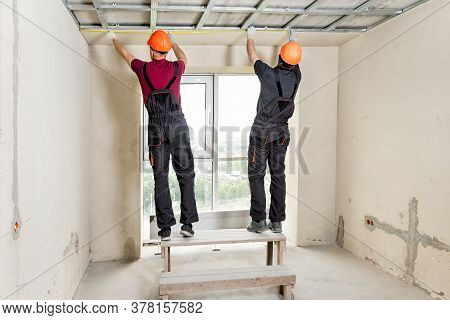 Installation Of Drywall. Workers Are Measuring The Ceiling.