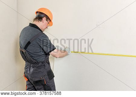 Installation Of Drywall. The Worker Is Measured To Cut Off A Piece Of Drywall Later.