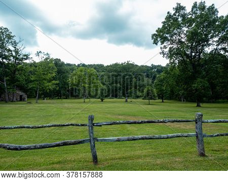 Scenic Landscape Nature Photo With A Wooden Fence In The Foreground And A Tree Line In The Backgroun