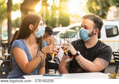Spain Madrid. Caucasian Couple Toasting With Beer Wearing Sanitary Mask. Reopen Pubs And Club After