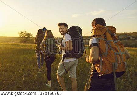 Hike. Hiking. Tourism.a Group Of Tourists With Backpacks Are Walking Along The Hill At Sunset In Nat