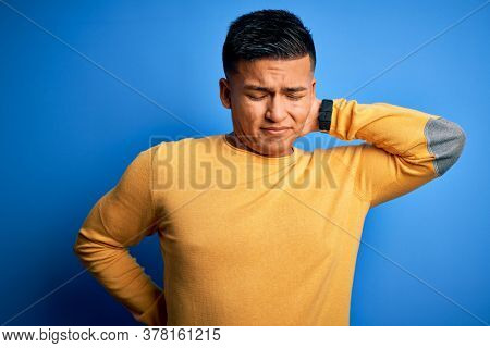 Young handsome latin man wearing yellow casual sweater over isolated blue background Suffering of neck ache injury, touching neck with hand, muscular pain