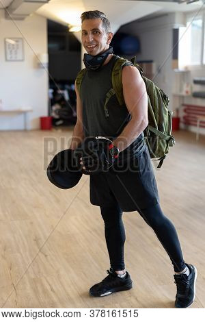 Portrait Of Smiling Instructor With Punch Mitts In Gym Hall. Attractive Sportsman Looking To Camera,