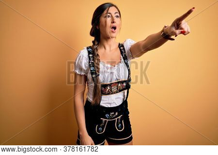 Young beautiful brunette german woman celebrating Octoberfest wearing traditional dress Pointing with finger surprised ahead, open mouth amazed expression, something on the front