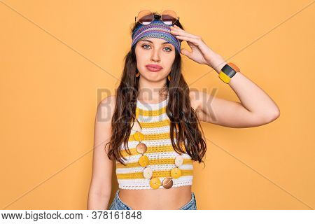 Young beautiful hippie woman with blue eyes wearing accesories and sunnglasses worried and stressed about a problem with hand on forehead, nervous and anxious for crisis