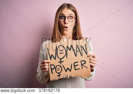 Young beautiful redhead woman asking for women rights holding banner over pink background scared in shock with a surprise face, afraid and excited with fear expression