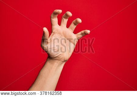 Hand of caucasian young man showing fingers over isolated red background grasping aggressive and scary with fingers, violence and frustration