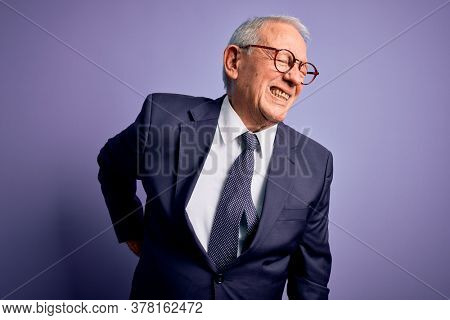 Grey haired senior business man wearing glasses and elegant suit and tie over purple background Suffering of backache, touching back with hand, muscular pain