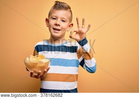 Young little caucasian kid eating unheatlhy potatoes crisps chips over yellow background doing ok sign with fingers, excellent symbol