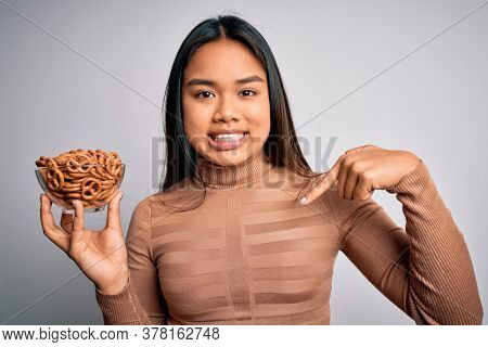 Young asian girl holding bowl with baked german pretzels over isolated white background with surprise face pointing finger to himself
