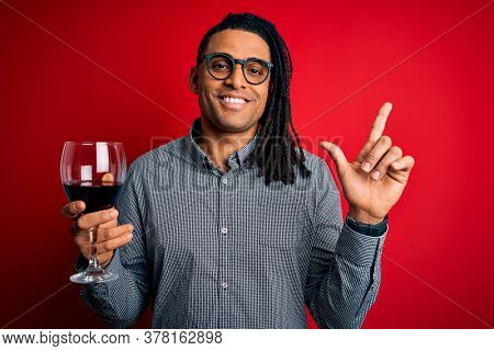Young african american afro sommelier man with dreadlocks drinking glass of wine surprised with an idea or question pointing finger with happy face, number one