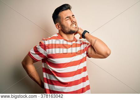 Young handsome man wearing casual striped t-shirt standing over isolated white background Suffering of neck ache injury, touching neck with hand, muscular pain