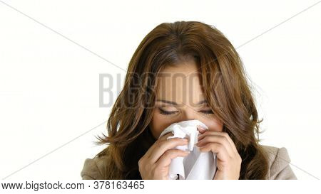 Ill business woman sneezing in tissue.