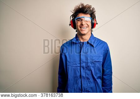 Young constructor man wearing uniform and earmuffs over isolated white background with a happy and cool smile on face. Lucky person.
