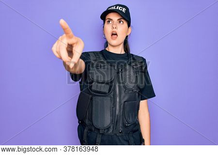 Young police woman wearing security bulletproof vest uniform over purple background Pointing with finger surprised ahead, open mouth amazed expression, something on the front