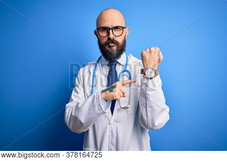 Handsome bald doctor man with beard wearing glasses and stethoscope over blue background In hurry pointing to watch time, impatience, looking at the camera with relaxed expression