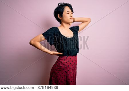 Young beautiful asian girl wearing casual dress standing over isolated pink background Suffering of neck ache injury, touching neck with hand, muscular pain