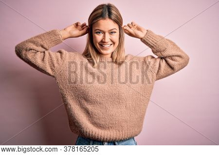 Young beautiful blonde woman wearing winter wool sweater over pink isolated background Smiling pulling ears with fingers, funny gesture. Audition problem