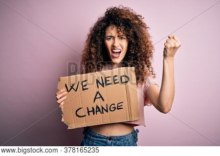 Young beautiful activist woman with curly hair and piercing protesting asking for a change annoyed and frustrated shouting with anger, crazy and yelling with raised hand, anger concept