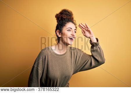 Young beautiful brunette woman with curly hair and piercing wearing casual dress very happy and smiling looking far away with hand over head. Searching concept.