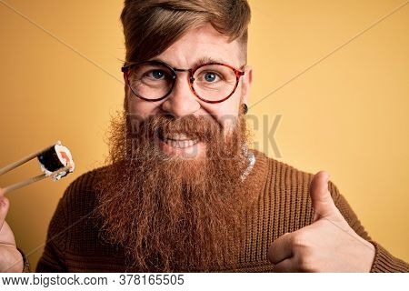 Redhead Irish man with beard eating salmon maki sushi using chopsticks over yellow background happy with big smile doing ok sign, thumb up with fingers, excellent sign