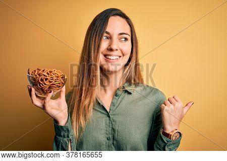 Young beautiful blonde woman with blue eyes holding bowl with german baked pretzels pointing and showing with thumb up to the side with happy face smiling