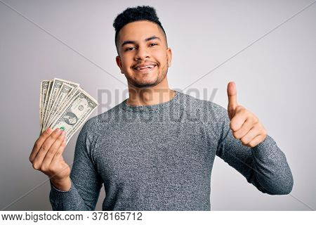 Young handsome man holding bunch of dollars banknotes over isolated white background happy with big smile doing ok sign, thumb up with fingers, excellent sign