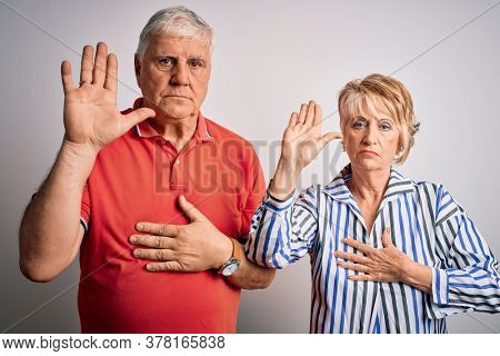 Senior beautiful couple standing together over isolated white background Swearing with hand on chest and open palm, making a loyalty promise oath