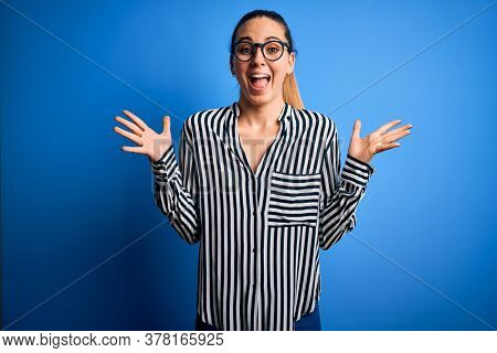 Beautiful blonde woman with blue eyes wearing striped shirt and glasses over blue background celebrating crazy and amazed for success with arms raised and open eyes screaming excited. Winner concept