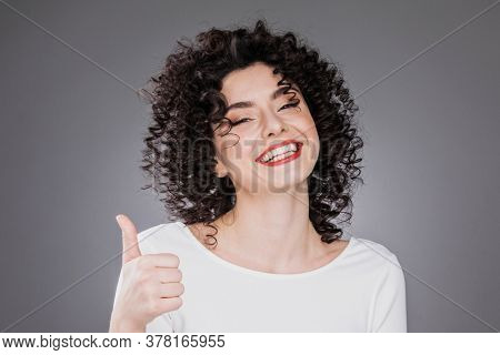 Happy smiling excited woman giving thumb up. Caucasian female with curly hair and toothy smile on gray background