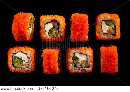 California rolls sushi with salmon, cucumber, avocado, cream cheese, red masago caviar over black background. Sushi menu, Japanese food. Top view
