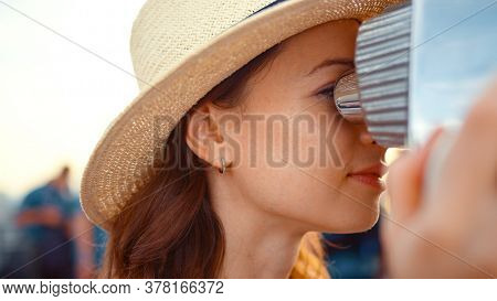 Young tourist looking through binoculars at the view point