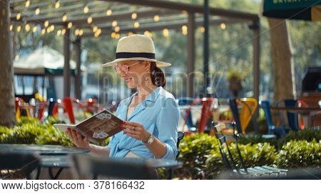 Attractive woman with a travelbook in park, NYC