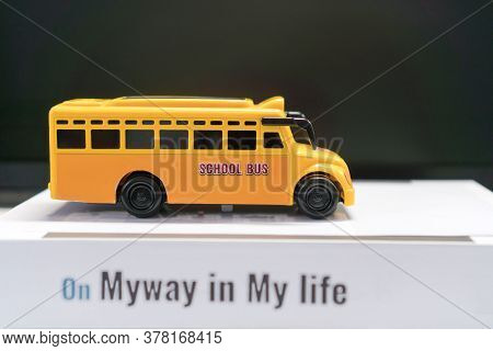 Yellow School Mini Bus Toy Concept,student Transport For Children Transports Service On Stack Books